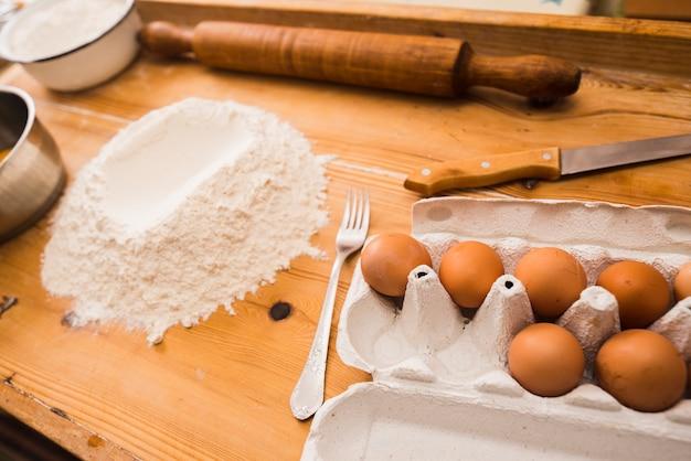 Uova e farina sul ripiano del tavolo in legno