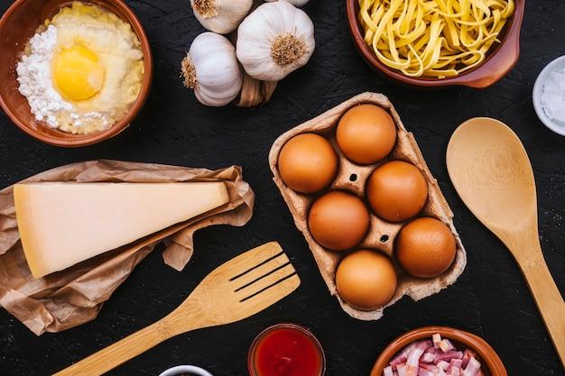 Uova e formaggio tra gli ingredienti e gli utensili per la pasta