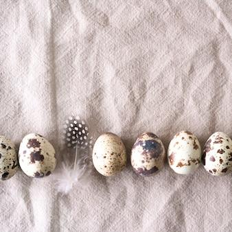 Uova e piume di quaglia di pasqua su fondo di tela naturale. sfondo di pasqua