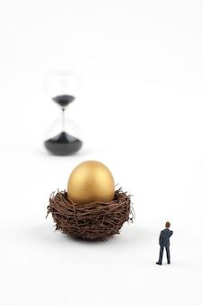 Uova e uomo dorati di affari su fondo bianco