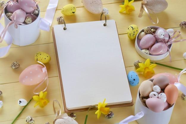 Uova, fiori gialli dei narcisi del blocco note sul fondo di legno del bordo giallo