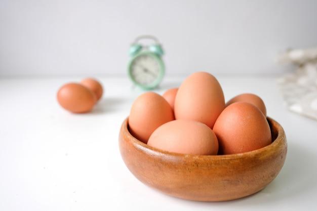 Uova fresche dall'azienda agricola disposte su un fondo di tavolo in legno bianco