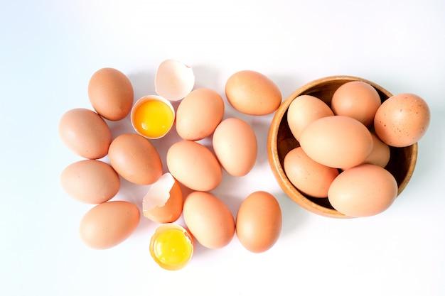 Uova fresche dall'azienda agricola disposte su una tavola di legno bianca
