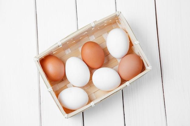 Uova fresche in un cestino su una priorità bassa di legno.