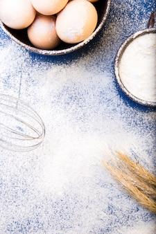 Uova fresche in una ciotola, frullino per le uova, grano su farina