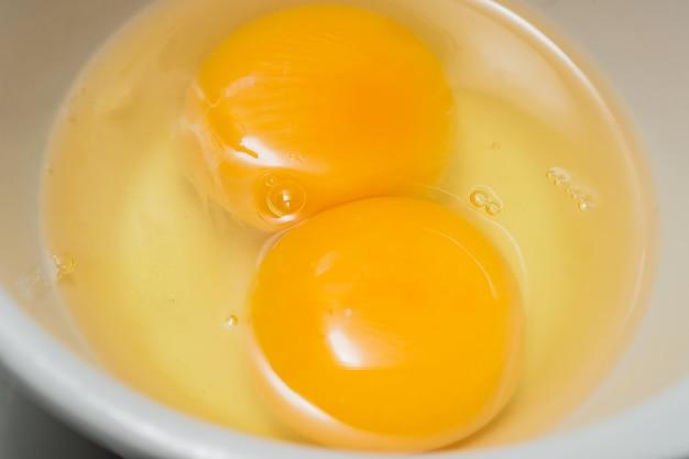 Uova fresche, tuorlo d'uovo gemello in ciotola di vetro