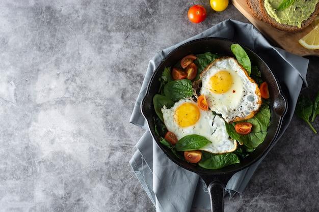 Uova fritte al sole con spinaci, toast di avocado e pomodori freschi, cibo per la colazione sano,