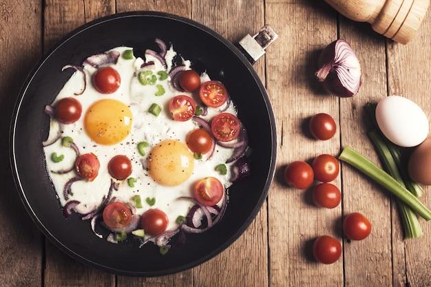 Uova fritte con le verdure sulla tavola di legno rustica