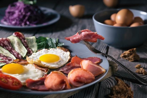 Uova fritte con pancetta e verdure su un piatto blu