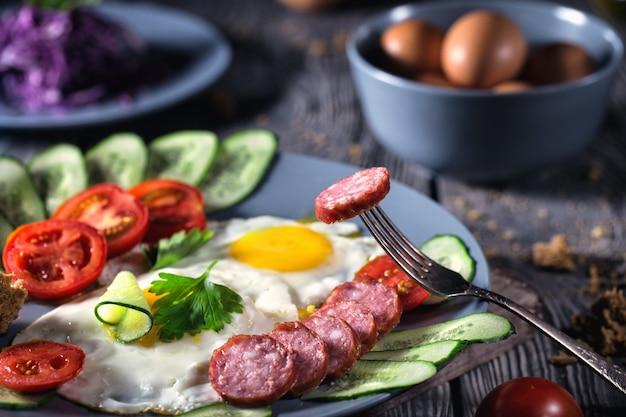 Uova fritte con verdure e salsiccia