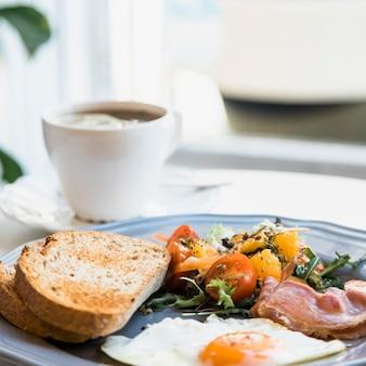 Uova fritte fatte in casa; insalata e pancetta sul piatto davanti alla tazza di caffè