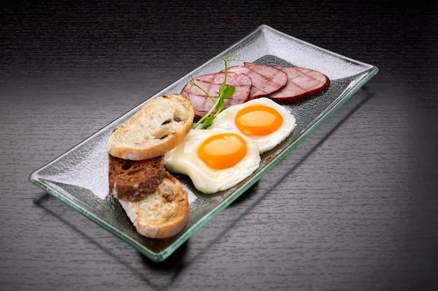 Uova fritte fritte con pomodori, prosciutto e pane tostato ciabatta, su una superficie scura. colazione