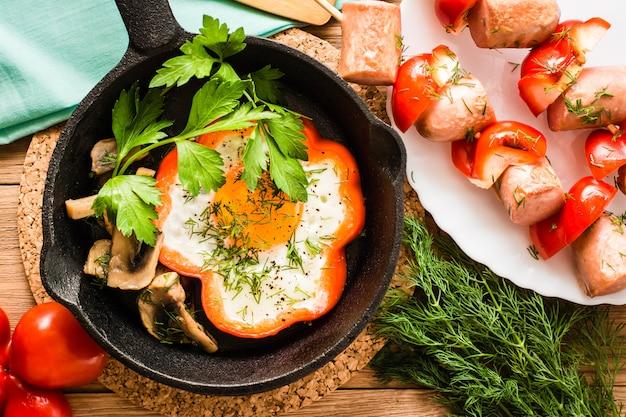 Uova fritte in pepe nella padella e le salsicce con peperoni su spiedini su un piatto