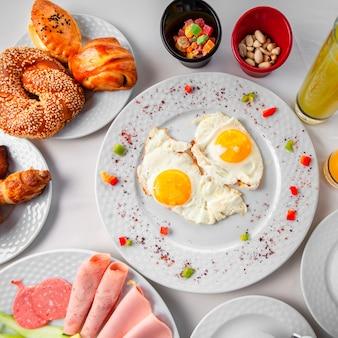 Uova fritte in un piatto con altri pasti vista dall'alto su uno sfondo bianco