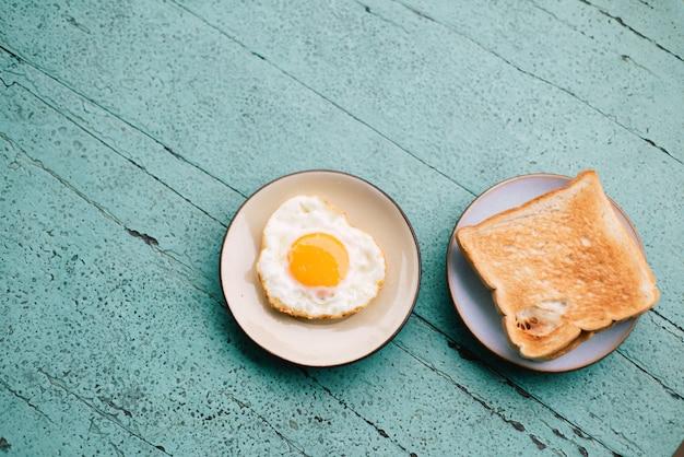 Uova fritte, pane tostato, caffè, set da colazione posto su un tavolo di legno blu