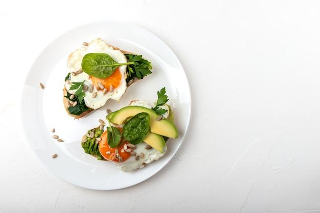 Uova fritte su un pane tostato con avocado, spinaci e semi su uno sfondo bianco piatto