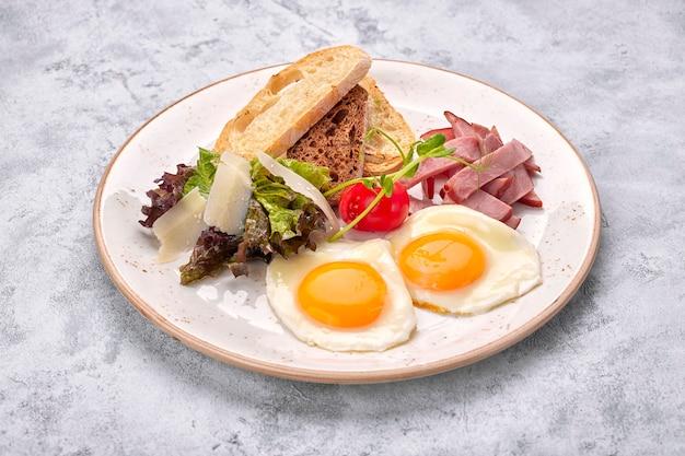 Uova fritte uova fritte con pomodori, prosciutto e pane tostato ciabatta, su una superficie bianca. colazione