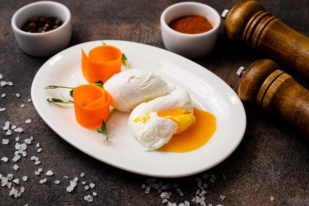 Uova in camicia su un piatto bianco su un tavolo nero