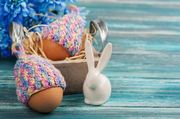 Uova in cappelli lavorati a maglia, fiori e coniglio decorativo