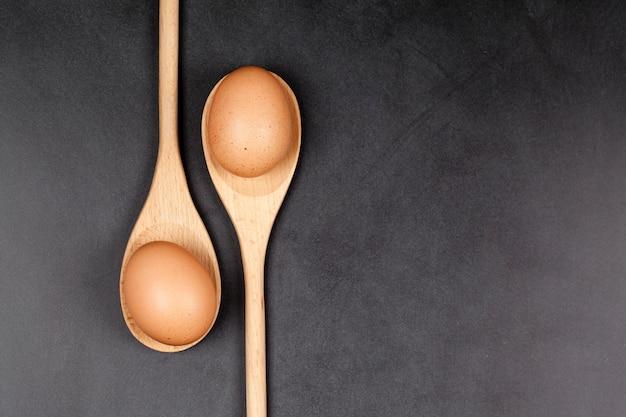 Uova in cucchiai di legno. utensile da cucina per torta, pasticceria o biscotti su sfondo di tabellone.