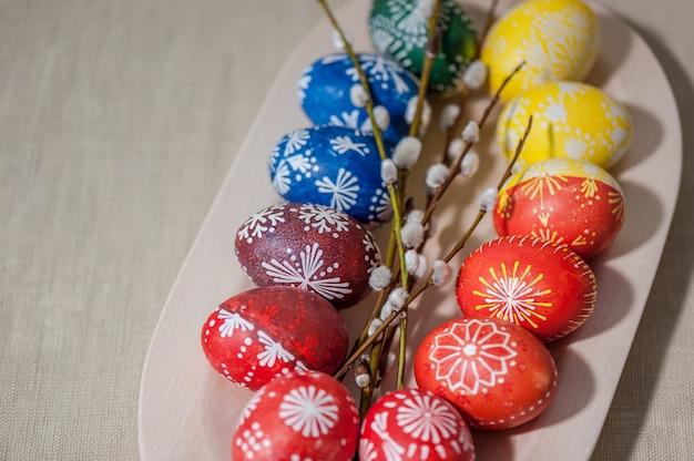 Uova in piatto di legno, dipinte con cera. concetto di vacanza di pasqua.