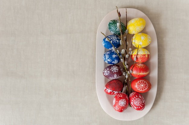 Uova in piatto di legno, dipinte con cera e colori alimentari. concetto di vacanza di pasqua.
