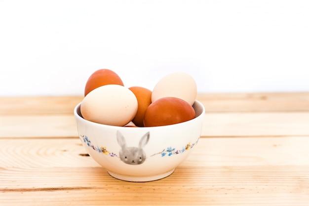 Uova in una ciotola di ceramica, piatto su uno sfondo di legno, preparando per pasqua, prodotti agricoli, pollo e uova, decorando la casa per le vacanze