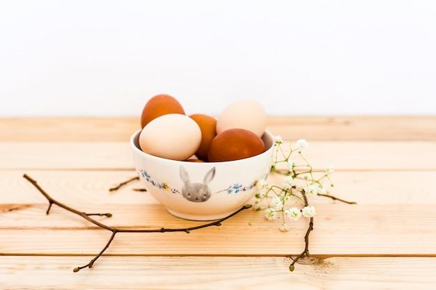Uova in una ciotola di ceramica, piatto su uno sfondo di legno, preparazione per pasqua, prodotti agricoli, pollo e uova, decorazione della casa per le vacanze, rami di un albero con gemme, primavera