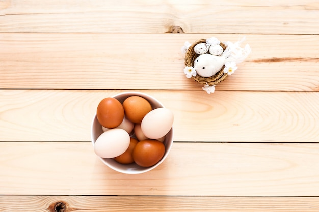 Uova in una ciotola di ceramica, piatto su uno sfondo di legno, preparazione per pasqua, prodotti agricoli, pollo e uova, figurina di un uccello in un nido, decorare la casa