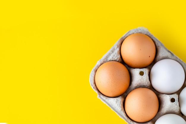 Uova in una scatola di cartone, in un vassoio. vassoio con uova su uno sfondo giallo.