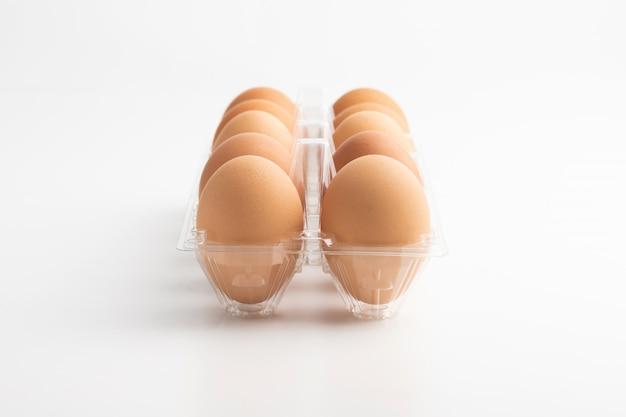 Uova in una scatola libera sui precedenti bianchi