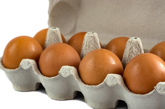 Uova in vassoio isolato su bianco