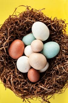 Uova luminose di festa di pasqua nel nido su superficie gialla, celebrazione della molla