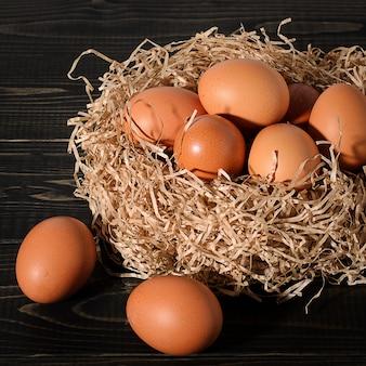 Uova marroni fresche su fondo rustico, di legno, nero, scuro nel nido.