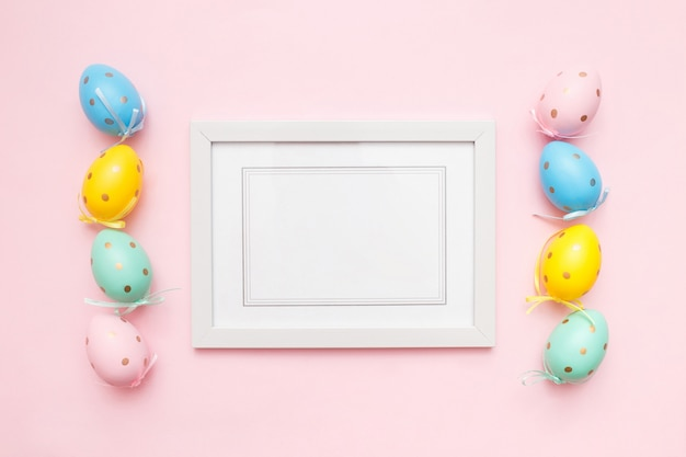 Uova multicolori di pasqua e struttura bianca della foto sul rosa