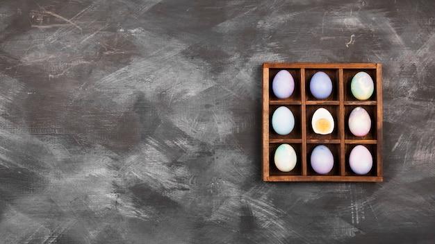 Uova multicolori per pasqua su sfondo nero. vista dall'alto, copia spazio. sfondo di cibo
