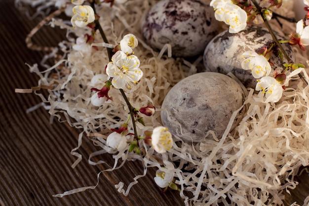 Uova pasquali colorate nel nido con brunch fioriti