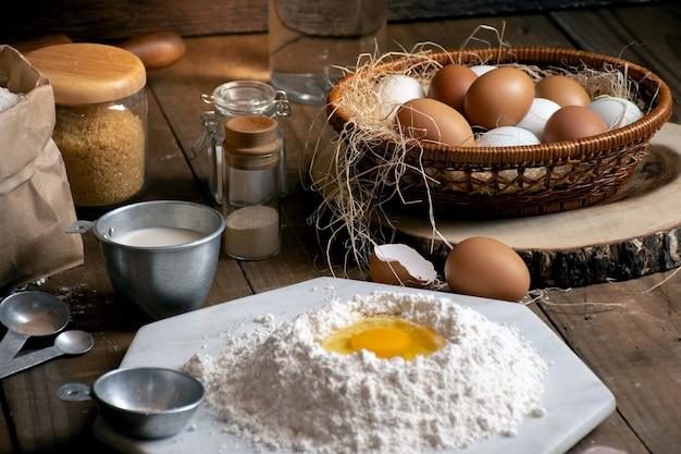 Uova, pasta e farina sulla tavola di legno con fondo splat per un oggetto in un forno