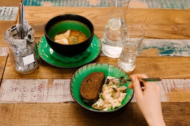 Uova rimescolate in una ciotola di acqua, accanto alla minestra, menu del pranzo su una tavola di legno, fuoco selettivo