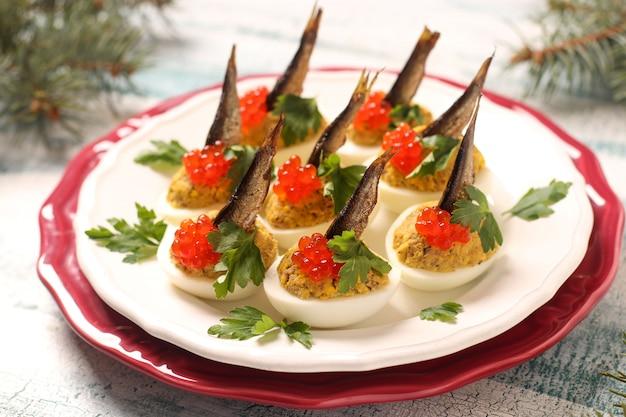 Uova ripiene di spratti e caviale rosso su un piatto bianco. merenda festiva