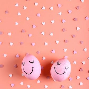 Uova rosa con sorrisi dipinti sullo sfondo con cuori, auguri di buona pasqua.