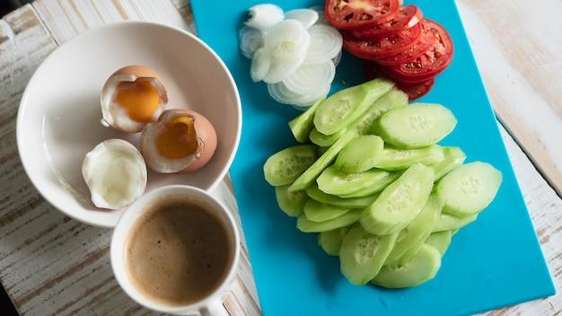 Uova sode con l'insieme fresco della prima colazione della tazza di caffè e dell'insalata del cetriolo - concetto dell'alimento di prima colazione di vista superiore