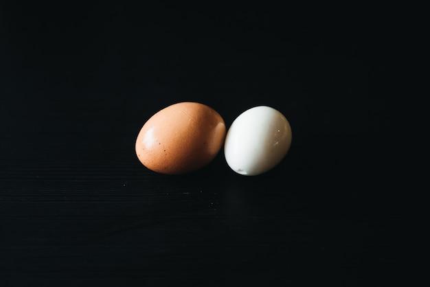 Uova sode fresche con guscio accanto a bordo di legno nero (attenzione selettiva)