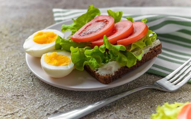 Uova sode tagliate a metà e sandwich con pane di segale, crema di formaggio, pomodori a fette e lattuga fresca per una sana colazione / pranzo.