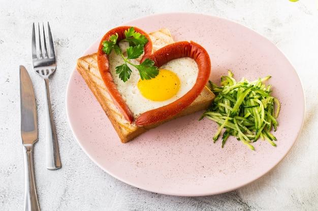 Uova strapazzate a forma di cuore su un piatto bianco con salsicce, pane tostato a lievitazione naturale isolato su sfondo di marmo bianco. cibo fatto in casa. gustosa colazione messa a fuoco selettiva. foto di hotizontal.