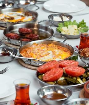 Uova strapazzate con pomodori e salsicce fritte