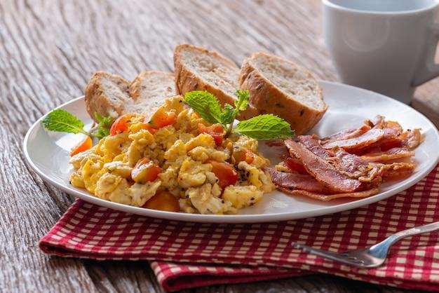 Uova strapazzate con pomodoro affettato, pancetta grigliata e pane, colazione fatta in casa.
