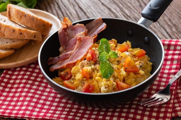 Uova strapazzate con pomodoro affettato, pancetta grigliata in padella e pane, colazione fatta in casa.