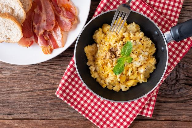 Uova strapazzate in padella con pane e pancetta alla griglia, colazione fatta in casa. vista dall'alto.