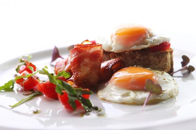 Uova strapazzate servite con pancetta e verde